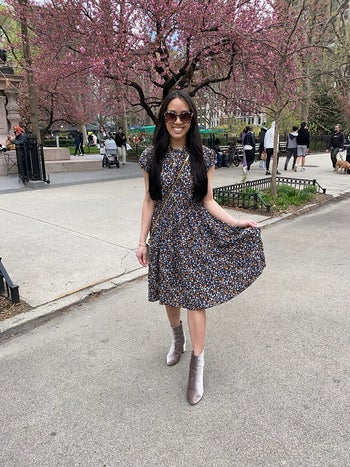another reviewer wearing the black version with small florals and a pair of gray velvet booties