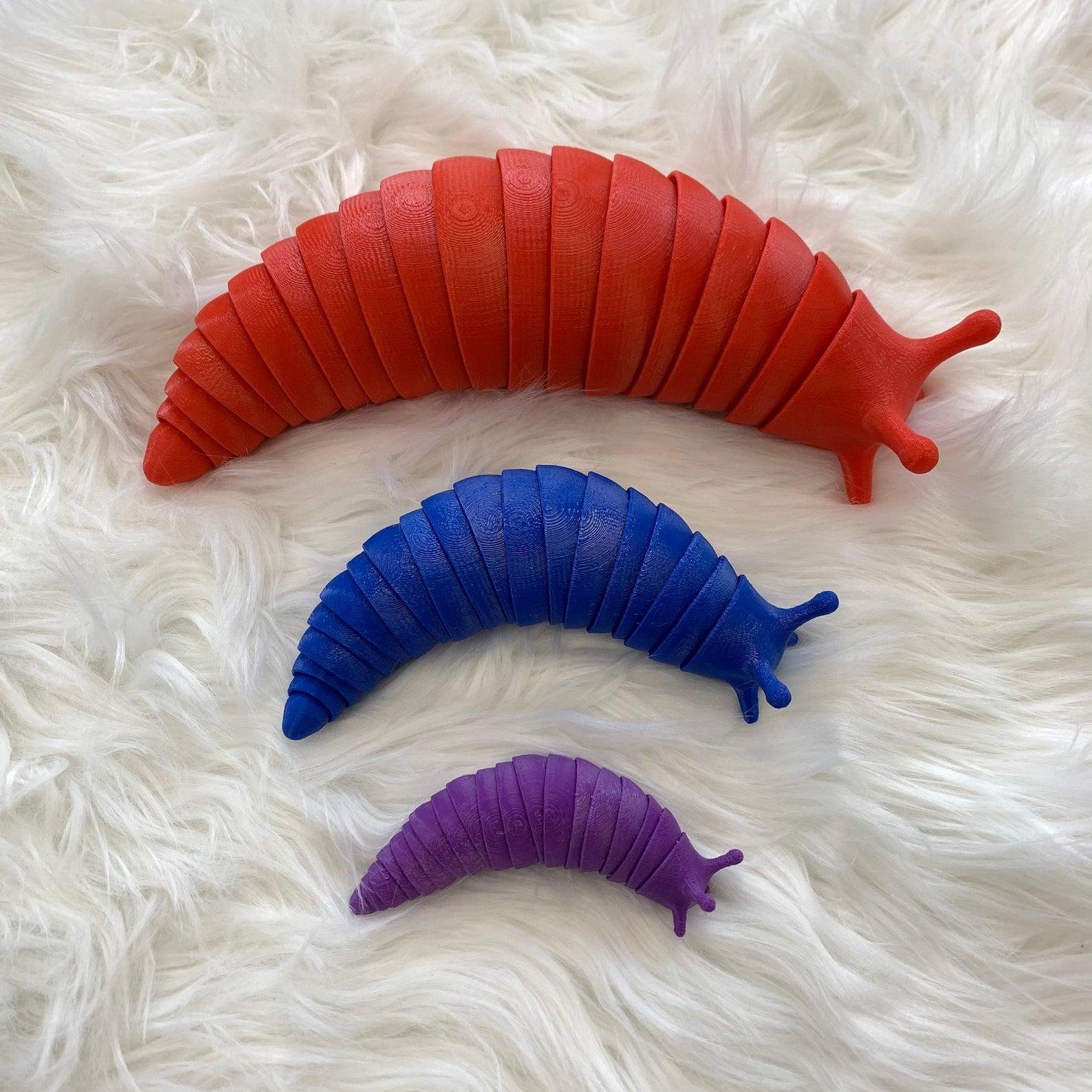 a red, a blue, and a purple slug fidget toy