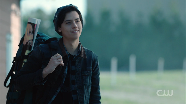 a teen wearing a jean jacket, backpack, and beanie smiles