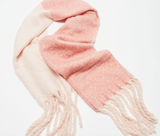 a pink and white scarf with tassels on the end