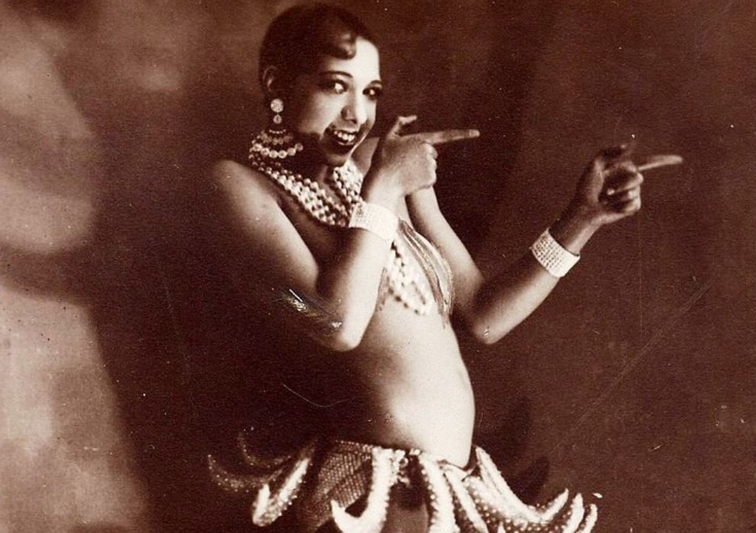 A woman with short hair is pointing to the right of the photo. She wears a lot of dangling jewelry and a skirt that looks like it has mini octopus tentacles