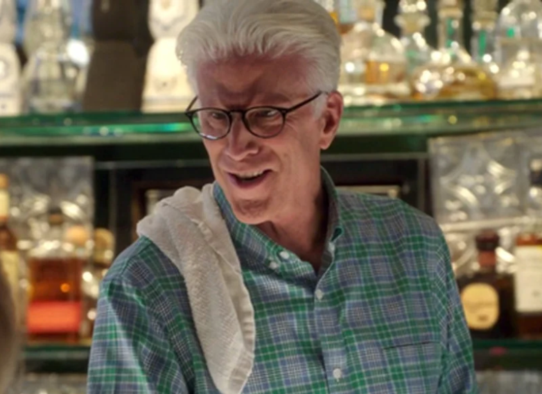 A man wears a button down shirt with a towel draped over his shoulder. He stands behind a bar. He wears glasses and is looking at someone off-camera