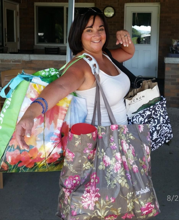 a reviewer photo of someone carrying several bags on their shoulder using the bag carrier