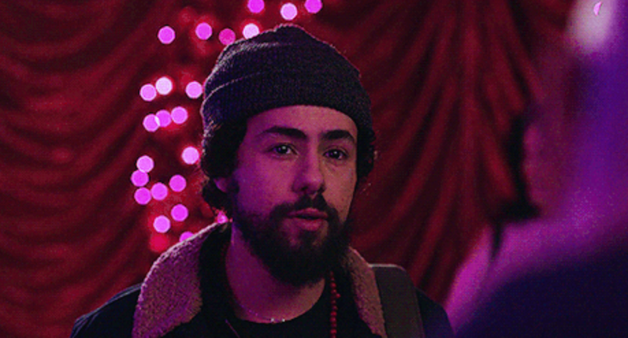 A man with a beard and curly hair wears a wool beanie hat and a jacket with a shearling fabric around the neck