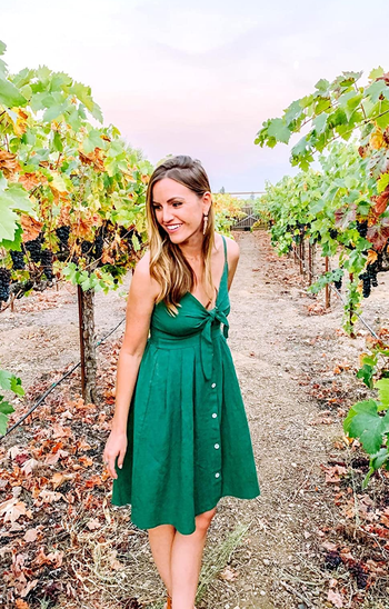 reviewer wearing the button front dress in green