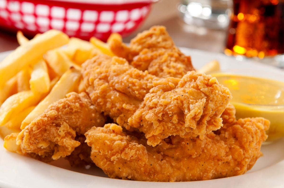Chicken tenders on a plate with fries and honey mustard sauce
