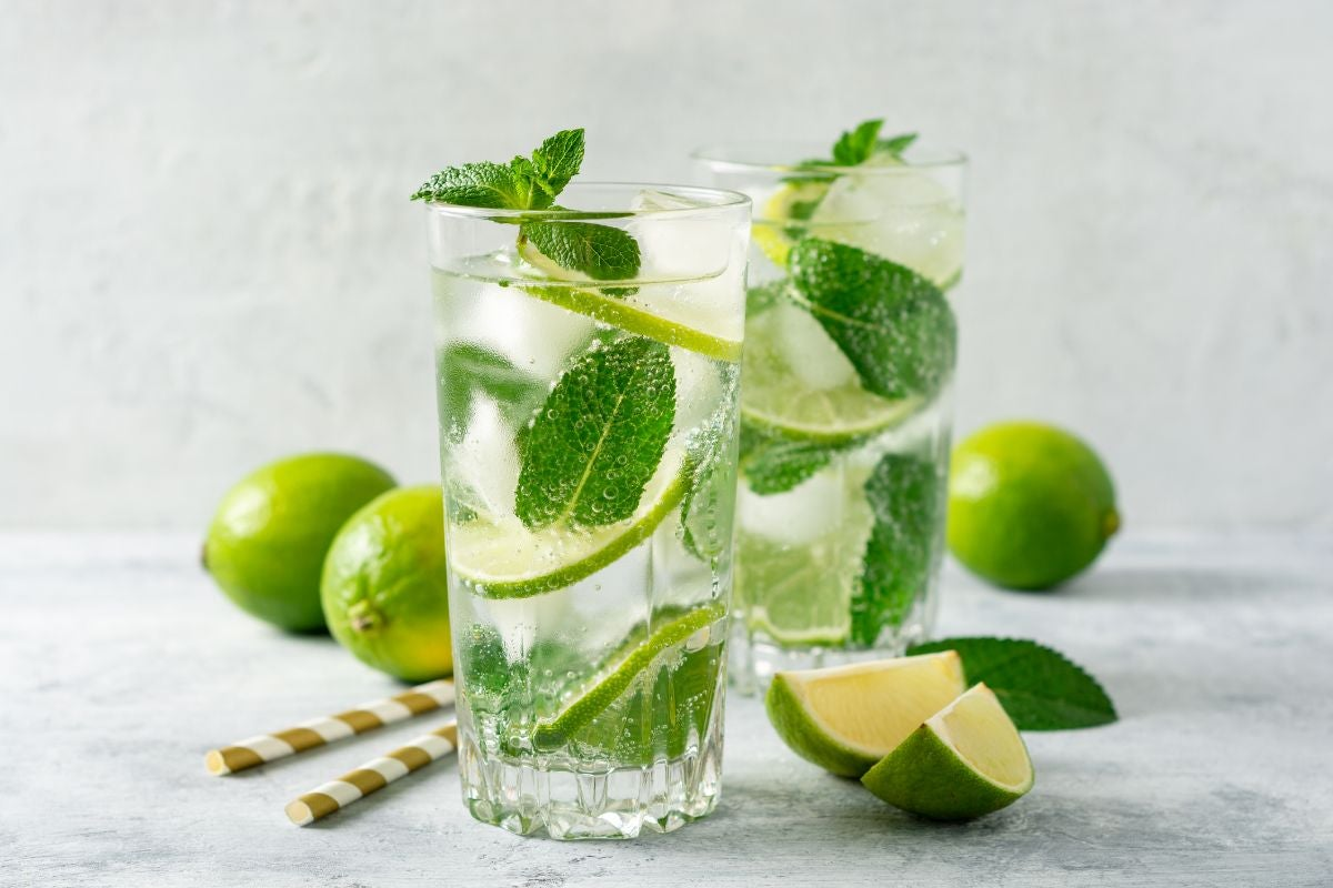 Two glasses of mojito in a grey kitchen decorated with mint leaves and limes