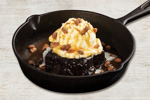 A brownie in a skillet with fudge, vanilla ice cream, caramel sauce, and nuts