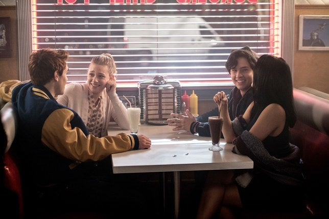 four teens sit at a diner table, laughing