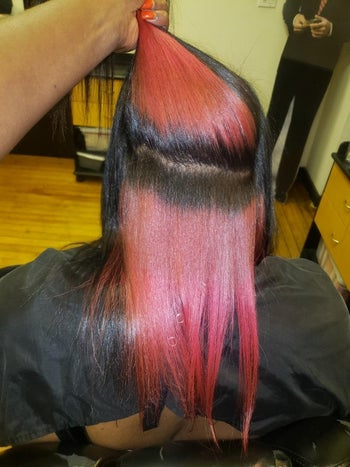 reviewer with straightened natural hair showing how vibrant the red is on their black hair