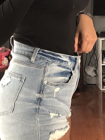 reviewer shows denim shorts too big on waist before using extra jean button