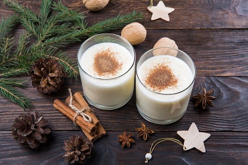 Two glasses of eggnog are sitting on a wooden table with Christmas decorations