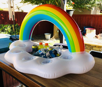 reviewer using rainbow float to hold drinks