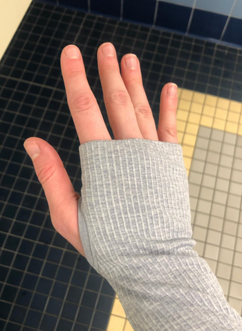 Reviewer showing sleeve of gray version with their thumb in the hole