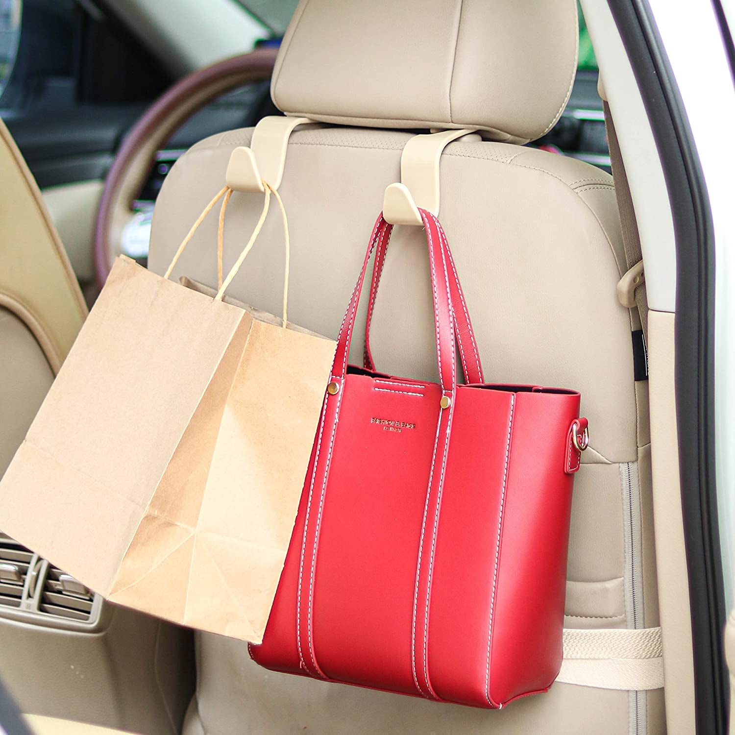 beige car seat headrest hook holding up a brown bag and red tote bag