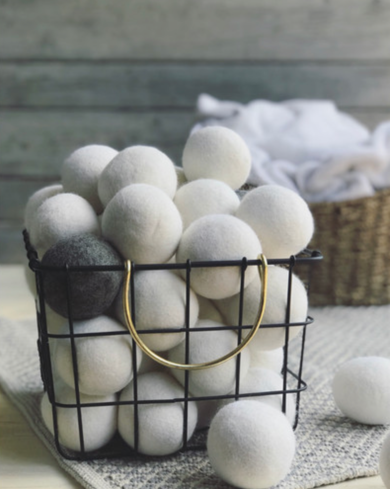 A metal basket with lots of white wool dryer balls in it