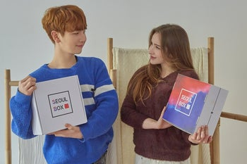 two people holding the seoul box