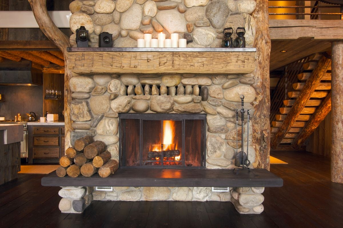 A stone fireplace with a wooden bench in front of it with logs on top of it
