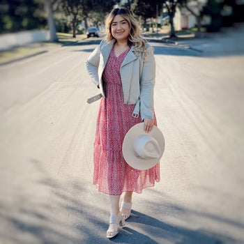 another reviewer wearing the pink and white dress with a gray leather jacket and white heels