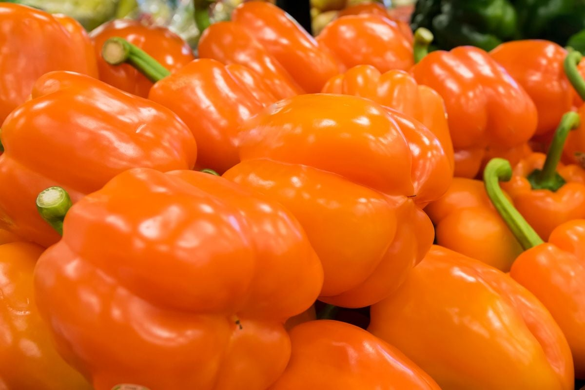 A stack of orange bell peppers in a supermarket display