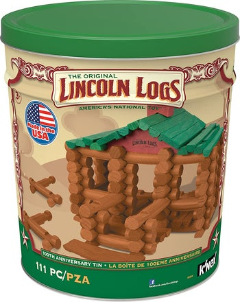A large round green tin filled with Lincoln logs