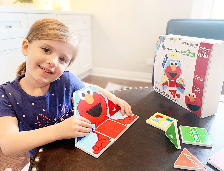 Child model playing with Elmo Magnatile set