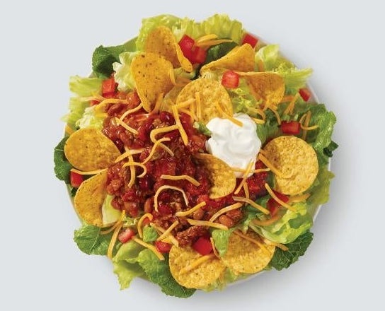 A salad with tortilla chips, cheese, chili, tomatoes, salsa, and sour cream