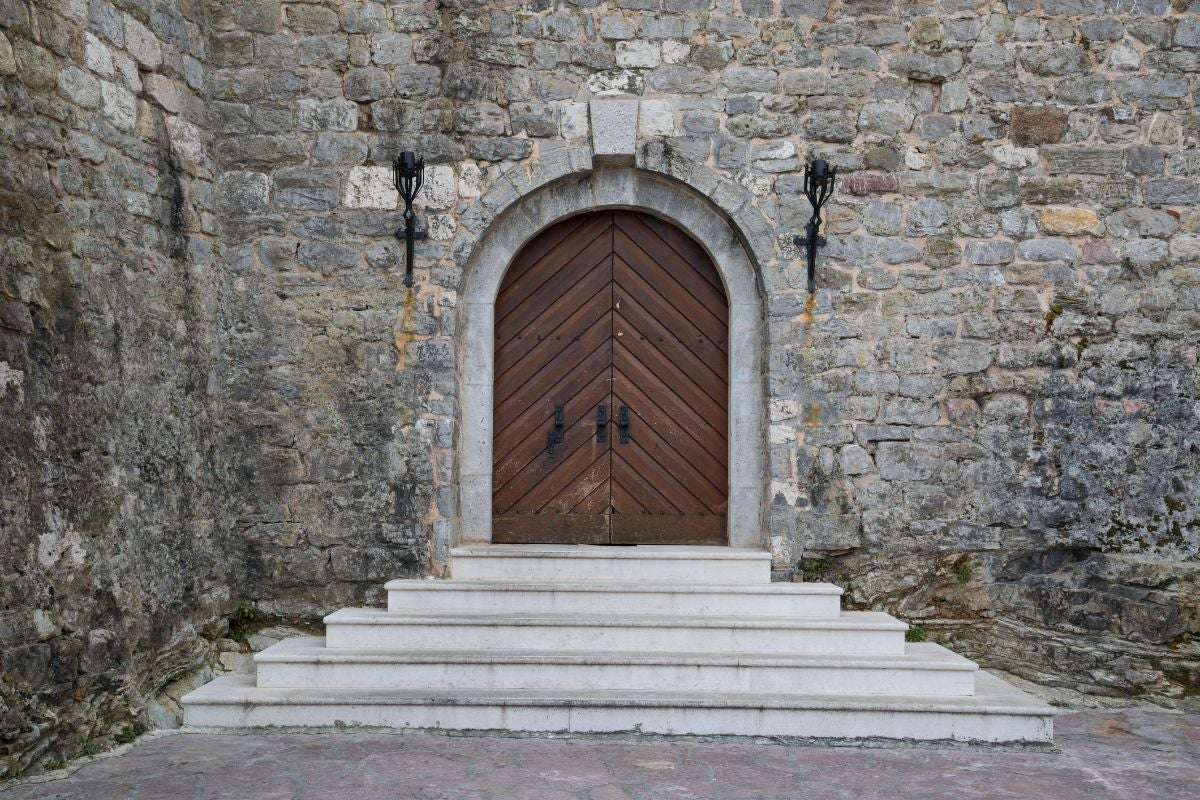 A grande entrance to a stone building with wooden double doors and pyramid-style steps leading up to the door