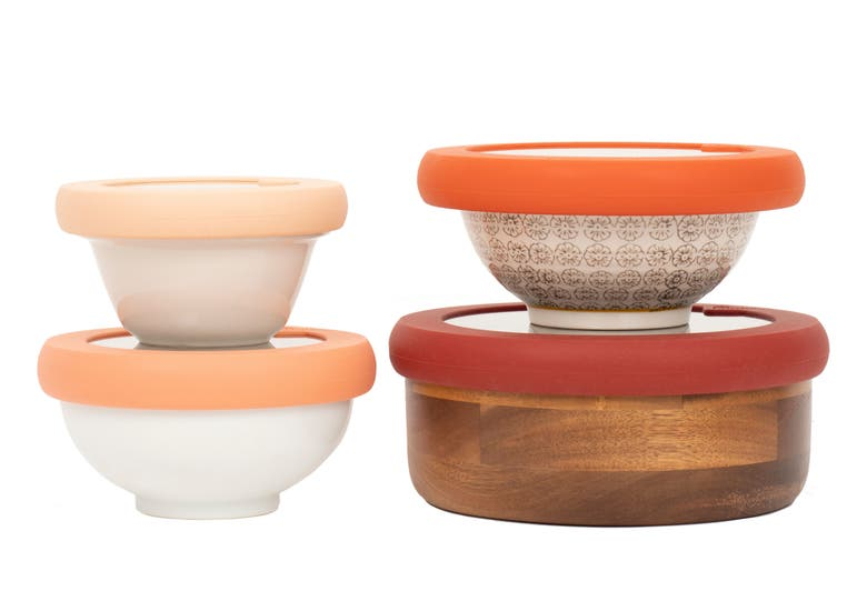 set of four bowls with silicone lids that are shades of orange