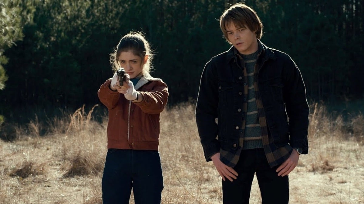 Nancy is holding a gun and Jonathan has his hands in his pockets