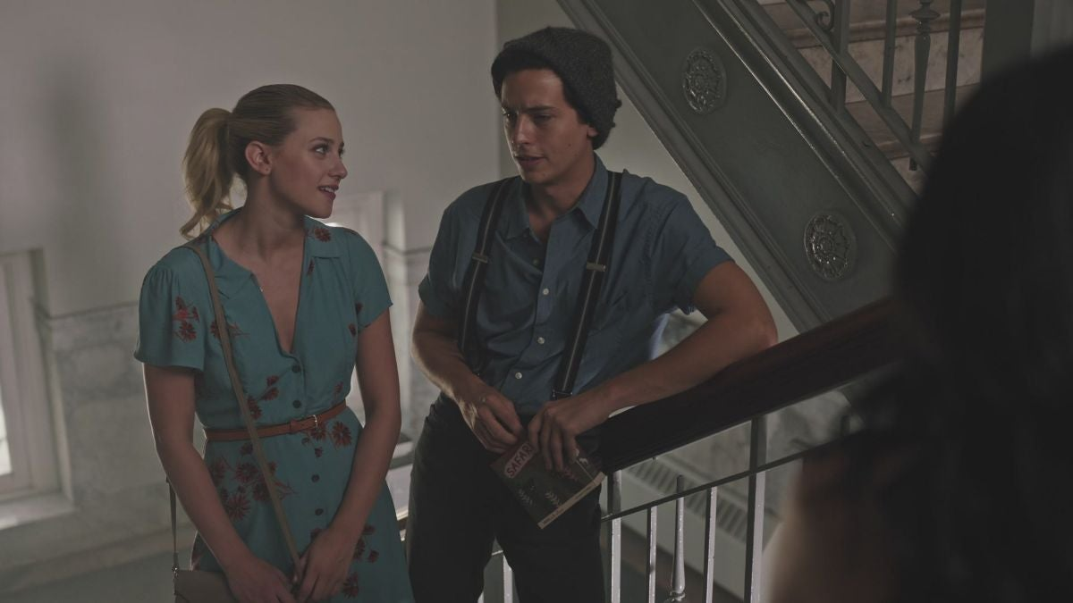 a teenage girl in a dress and ponytail and a teenage boy wearing a shirt and suspenders are in a stairwell