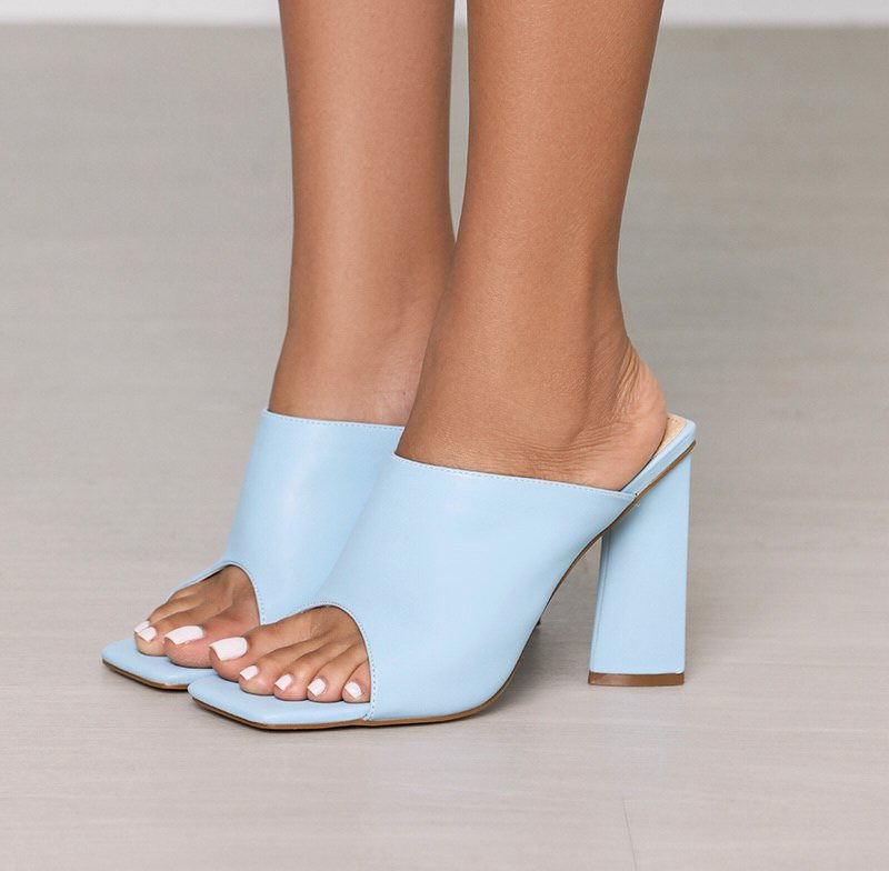 model wearing the square open-toe chunky heel shoes in light blue