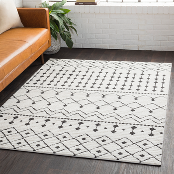 the white and black area rug in a living room, next to a couch