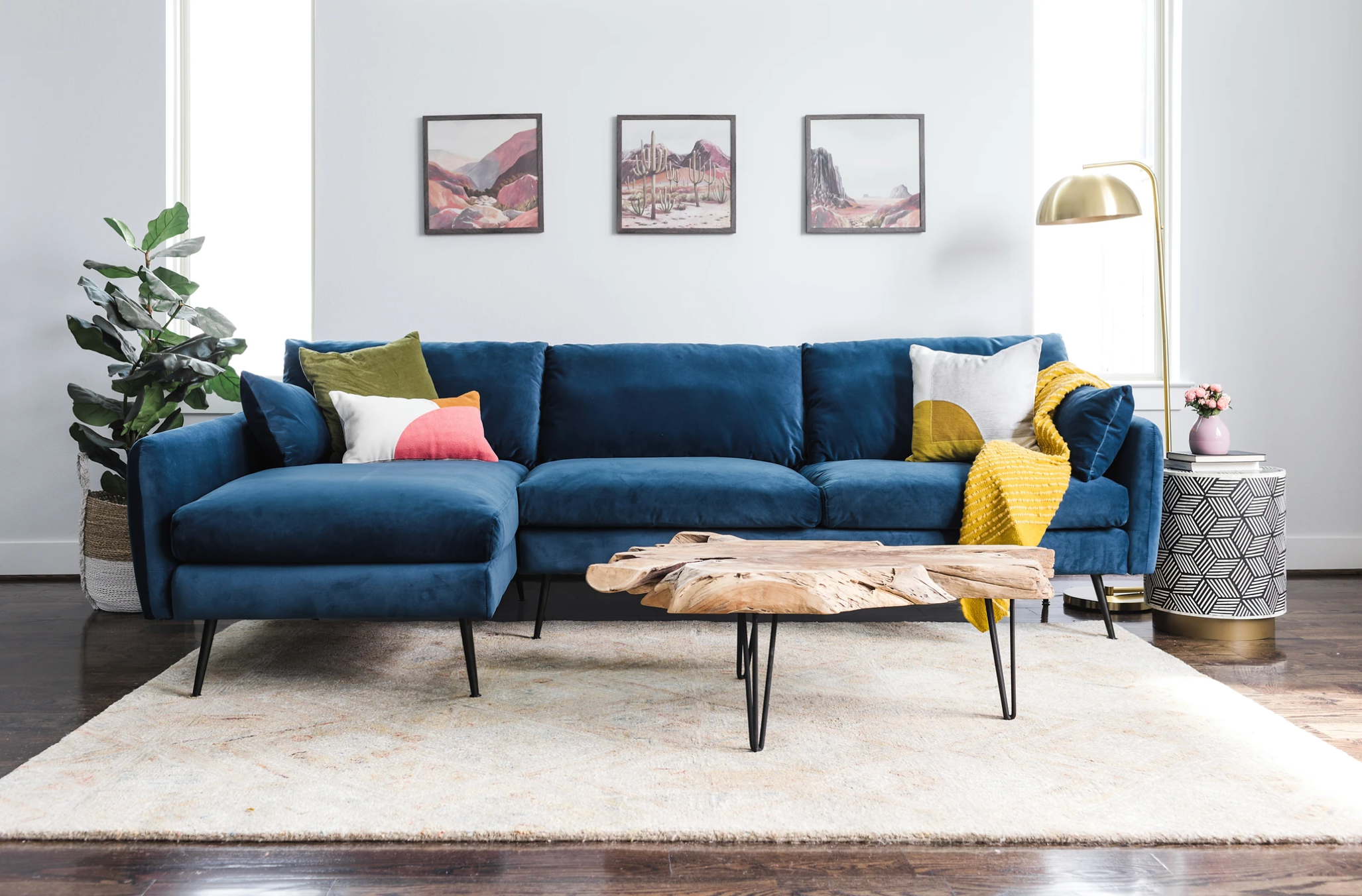 The albany park sectional in navy blue velvet is in a living room