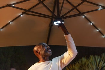 a model adjusting the lighting in the umbrella