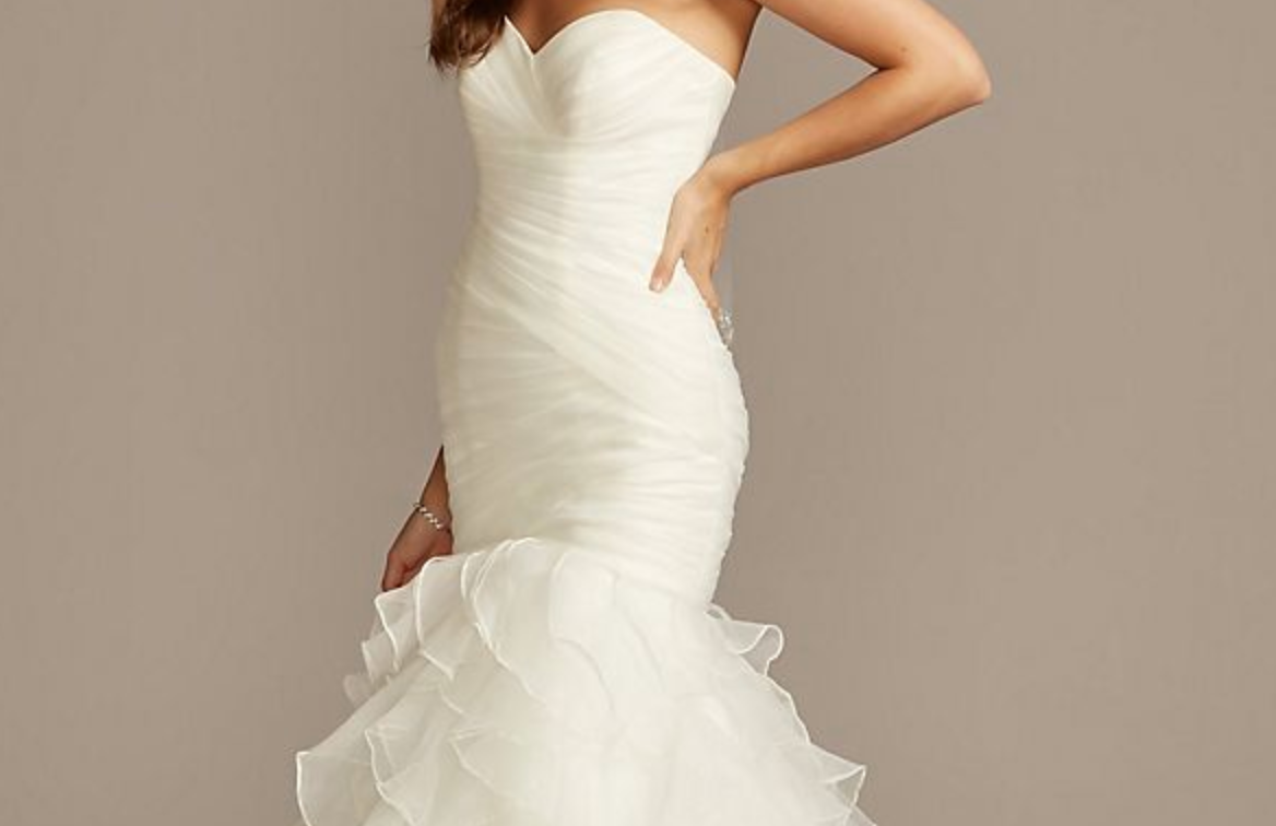 A strapless wedding dress with a fitted body and skirt that puffs out around the knees