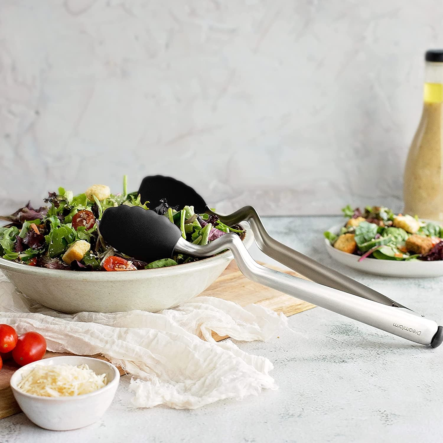 the tongs resting on a salad bowl