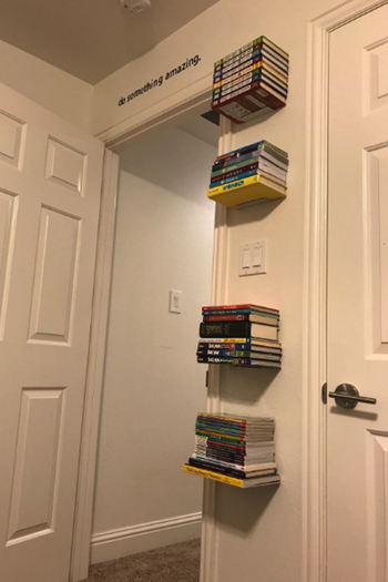 Reviewer photo of the bookshelves up on a wall with books on it