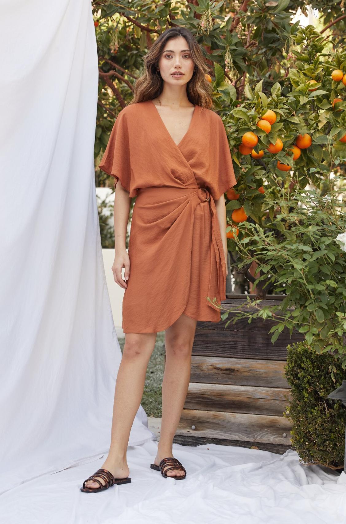 model wearing orange wrap dress