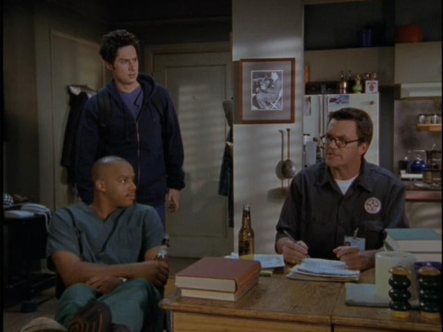 three men sit at a wooden table in an apartment