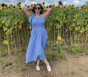 another reviewer wearing the dress in a sunflower field with white oxfords