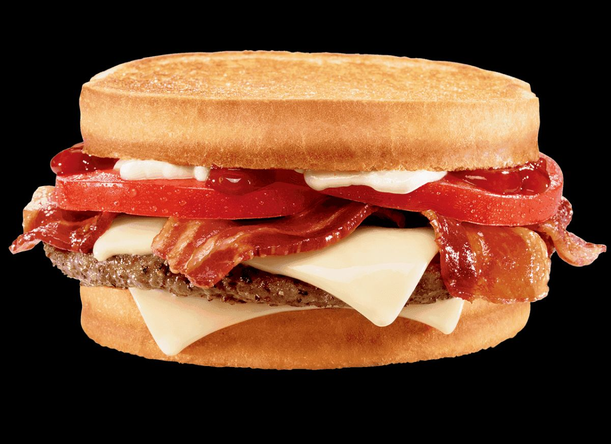 A burger on a sourdough bun with swiss cheese, bacon, tomato, ketchup, and mayo