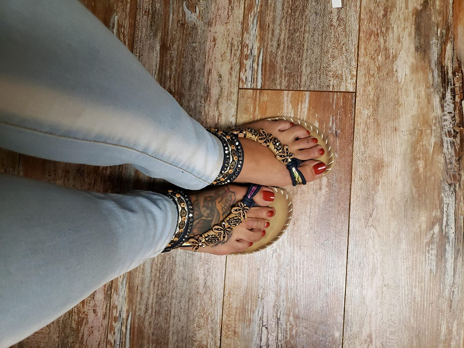 reviewer wearing the sandals with beaded ankle straps and butterfly beads across the foot