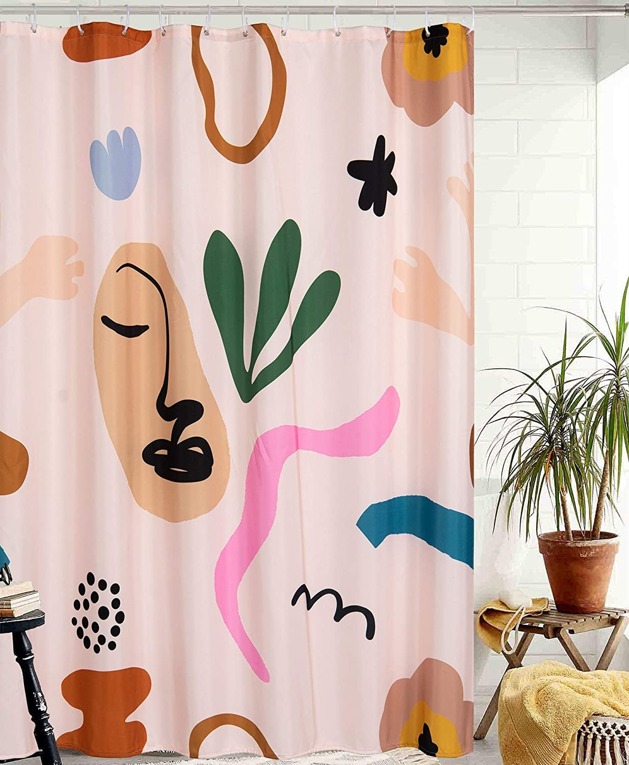 the pale pink shower curtain printed with colorful flowers, squiggles, and an abstract face
