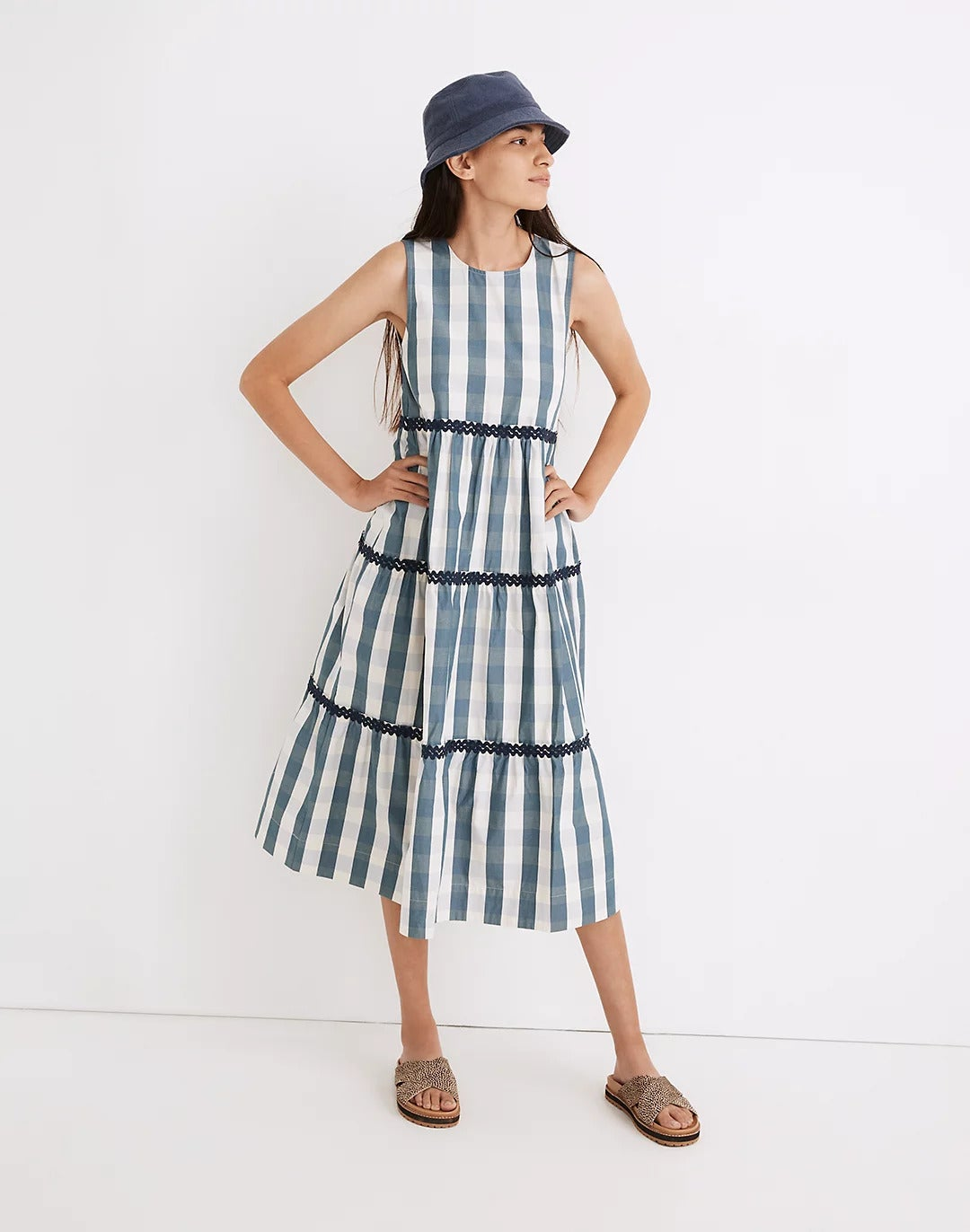 model wearing the blue and white check dress with crisscross sandals and a bucket hat