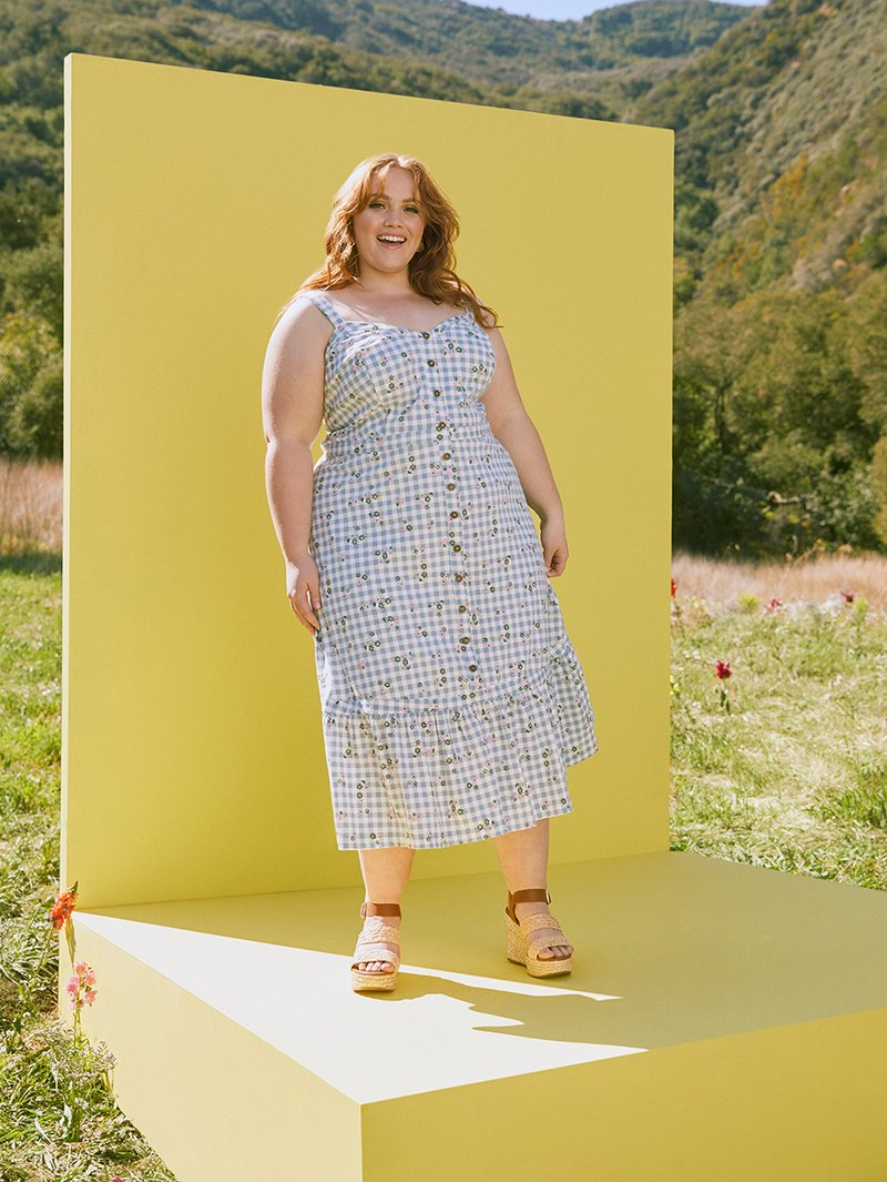 model in the sleeveless light blue and white gingham dress with with little green and white flowers