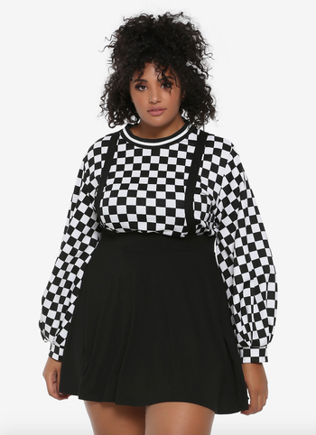 a model wearing a black skirt with suspenders over a checkerboard long sleeve