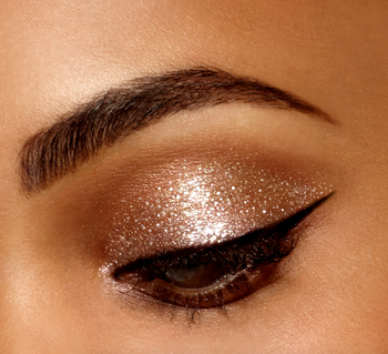 a model with a glittery gold eyelid