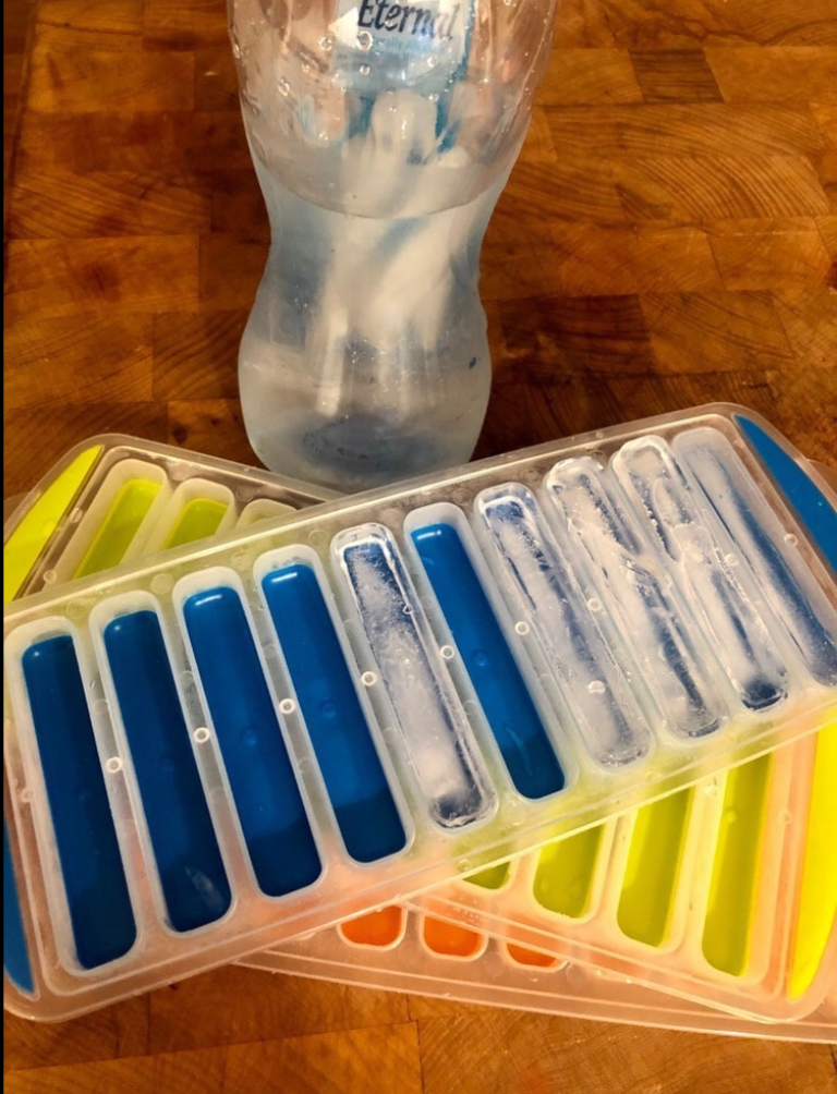 Reviewer image of three ice trays next to a water bottle with ice sticks in it