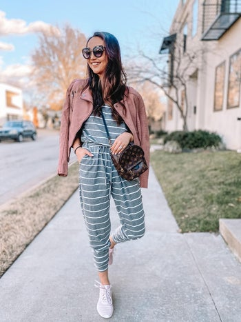 a reviewer wearing the jumpsuit in grey with white stripes